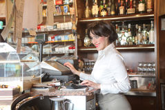 Bar. Smiling waitress standing behind the counter of a bar Stock Photo