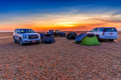 BAR AL HIKMAN, OMAN - OCT 30, 2015: Desert Camp Sunset. Sunset over the salt pan of Bar Al Hikman,  Al Wusta Governorate, Sultanate of Oman Royalty Free Stock Photo