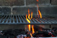 Bar b cue barbecue fire BBQ coal fire iron grill. Brick wall Stock Photos