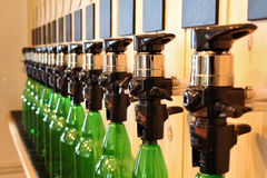 The bar beer spill. Beer Counter. Mass beer on tap. I poured a lot of beer bottles. Large simultaneous spilling beer in the bar. The bar of wood. Wooden desk stock images