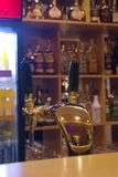 Bar with beer tap. And blurred bottles behind Royalty Free Stock Photography