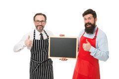 Bar cafe staff. Hiring staff. Men bearded hipster informing you. Men bearded bartender or cook in apron hold blank. Chalkboard. Bartender with blackboard royalty free stock images