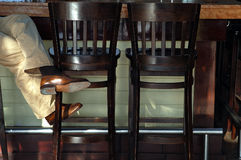 Bar and Chairs. Bar with two tall barstools or chairs, lower foot rail, man's legs propped on one of the stools Stock Photo