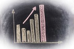 Bar chart sketched on blackboard. A bar chart with increasing trend and an arrow showing it explicitly is sketched with chalk on the blackboard stock photo
