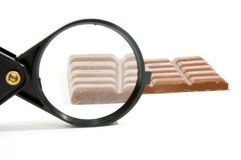 Bar of chocolat sized up by a magnifying-glass Stock Photography