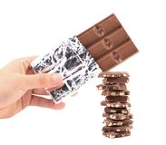 Bar of chocolate in foil and tasty morsel. Stock Image