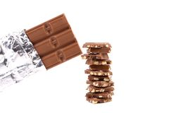 Bar of chocolate in foil and tasty morsel. Royalty Free Stock Photos