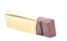 Bar of chocolate in gold foil. Royalty Free Stock Image