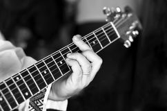 Barred Chord. Black and white picture of a musician holding a bar chord on an acoustic guitars fretboard Royalty Free Stock Photography