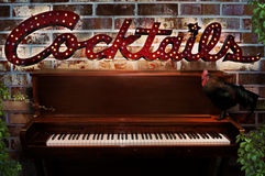 Piano bar cocktail sign. A cocktail sign on a brick wall with a piano and rooster.  Concept for an outside piano bar and entertainment Stock Images
