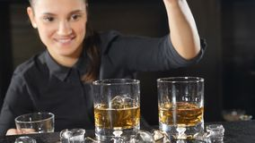 Bar concept. Female barmaid bartender waitress preparing alcohol cocktail dropping ice cube in slow motion. friendly. Smiling service bartender making drink stock video footage