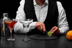 A bartender cuts a sappy green lime with a knife, a bar counter with glasses, oranges on a black background. Stock Image