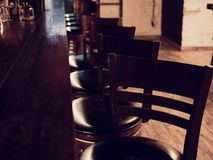 Bar counter with high chairs in empty cosy restaurant. Chairs in row in bar with lights royalty free stock image