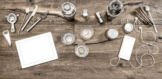 Bar counter with tools accessories devices Drink glasses. Bar counter with tools, accessories and electronic devices. Drink glasses on wooden table background Royalty Free Stock Images
