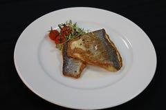 Bar de mer frit par casserole dans un plat blanc images libres de droits