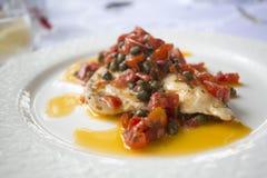 Bar de mer rôti avec des tomates et des câpres Image libre de droits
