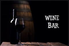 Bar de vinos Un vino rojo del opf de la botella y un vidrio con el barril en backg Foto de archivo