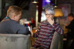 A in a bar and drinking beer, the girl covers mouth with hand. Indoors. royalty free stock photos