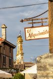 Bar El Alquimista signboard at Ages, Spain. AGES, SPAIN - MAY 16, 2017: Bar El Alquimista signboard and the church bell gable with a stork nest in the background stock image