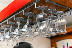 Bar glasses hanging in a row Royalty Free Stock Photos