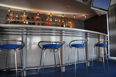Bar interior with round counter and stools Royalty Free Stock Photos