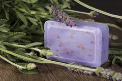 Lavender Soap Flowers. A bar of lavender soap surrounded with lavender plant leaves and flowers, soap is on rustic wood surface stock images