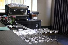 Bar with long counter. Many emply glasses and bottles with alcohol. Coffee machine at background stock images