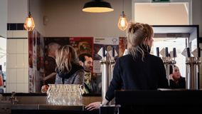 Bar maid in Brouwerij`t IJ Brewery in Amsterdam Netherlands. March 2015. Landscape format stock photos