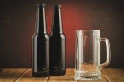bar med ett tomt exponeringsglas och flaskor av öl/baren med ett tomt exponeringsglas och flaskor av öl på en röd bakgrund royaltyfri fotografi
