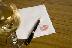 Bar message. Blank napkin, pen and a glass of whine on the foreground Stock Image