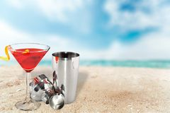 Metallic barman shaker with cocktail on sandy royalty free stock photos
