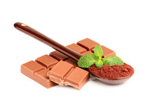 Bar of milk chocolate with a spoonful of cocoa. Stock Photography