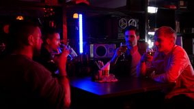 Bar with neon lighting. Friends spending time together, drinking beer. Cheers. Mid shot stock video footage