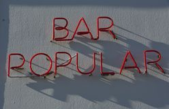 Bar popular in neon-light. On a blueish white wall , words Stock Image