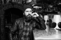 Bar is relaxing place to have drink and relax. Man with beard spend leisure in dark bar. Brutal lonely hipster. Brutal stock image