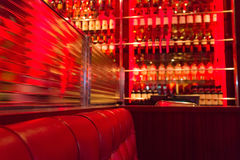 Bar Restaurant Leather Red Sofa and Wine Bottles. In the Background Royalty Free Stock Photography