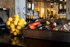 Bar scene set up with seafood and bowl of fresh lemons Royalty Free Stock Photo