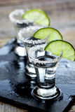 Bar set with shots, fresh lime and salt on wooden background. Bar set with silver tequila shots, fresh green lime and salt on wooden table background Stock Images