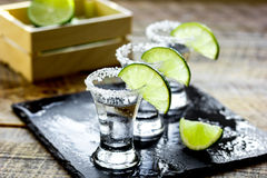 Bar set with shots, fresh lime and salt on wooden background. Bar set with silver tequila shots, fresh green lime and salt on wooden table background Stock Photos