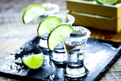 Bar set with shots, fresh lime and salt on wooden background. Bar set with silver tequila shots, fresh green lime and salt on wooden table background Stock Photo
