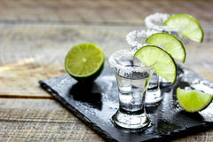 Bar set with shots, fresh lime and salt on wooden background Stock Images