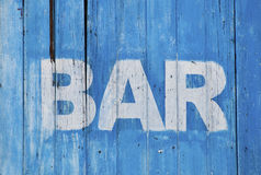 Bar sign. White bar sign painted on a dilapidated blue wooden wall Royalty Free Stock Photography