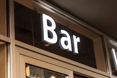 Bar sign. White neon-lighted bar sign above entry door Stock Photography