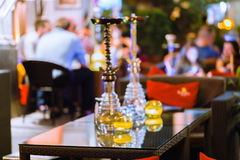 Bar for smoking a hookah. The background is blurred. In the foreground is a big hookah Royalty Free Stock Photography