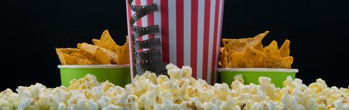 Bar snack for cinema, on a black background bucket nachos with video tape royalty free stock photo