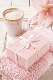 Bar of soap, bowl of sea salt, pink towel and lily flower Stock Photos