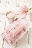 Bar of soap, bowl of sea salt, pink towel and lily flower Royalty Free Stock Photography