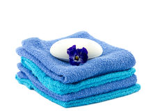 Bar of soap on piled towels and pansy flower Stock Image