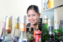 Bar staff and liqueurs. Waitress with whisky or liqueurs arround her royalty free stock photography