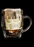 Bar staff tips in a pint glass. On black background royalty free stock photo